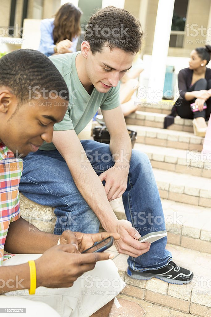 Technology: Young adults outdoors. Shopping or school steps. royalty-free stock photo