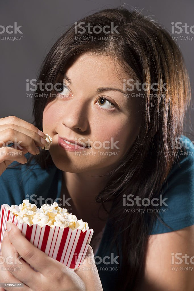 Technoloogy: Female watching TV.  Popcorn. royalty-free stock photo