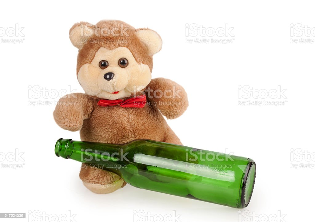 teddy bear and an empty bottle of beer foto