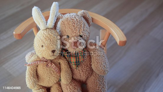 istock Teddy bear and bunny toy sitting on bench 1146404565