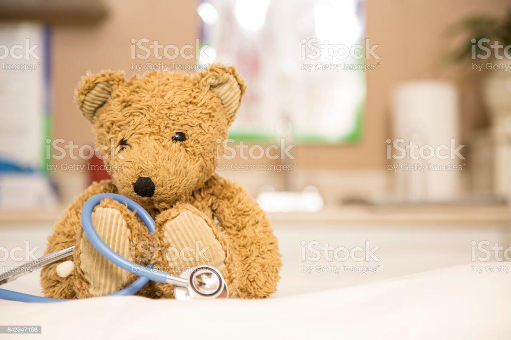 Ursinho de pelúcia e estetoscópio no consultório do pediatra. - foto de acervo