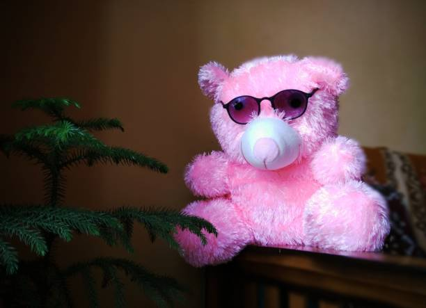 Teddy bear and tree Pink teddy bear wearing sunglasses . sitting on table near tree christmas teddy bear stock pictures, royalty-free photos & images