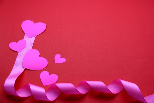 teddy bear, box of chocolates and pink hearts with ribbon on red background, Valentine's Day gifts, advertising banner
