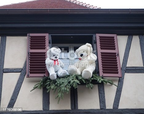Christmas decorations and teddy bears in the window of an unrecognisable building. Features altered to de identify structure