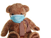 Cute teddy bear wearing PPE during the covid-19 Coronavirus pandemic. Taken in a studio on a white background.