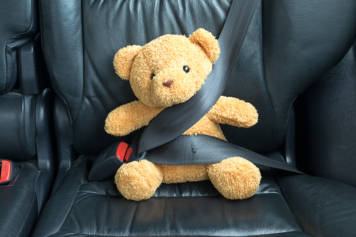 istock Teddy bear fastened in the back seat of a car 616247450