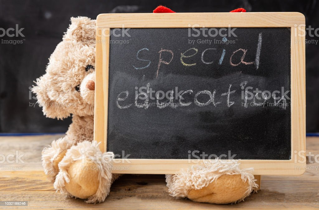 Teddy bear hiding behind a blackboard. Special education text drawing on the blackboard - foto stock