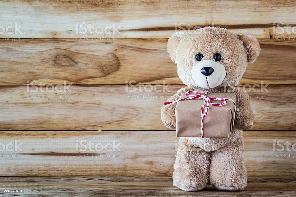Teddy bear holding a gift box stock photo