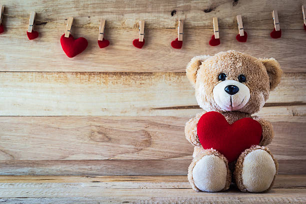 teddy bear holding a heart-shaped pillow - teddy bear stock photos and pictures