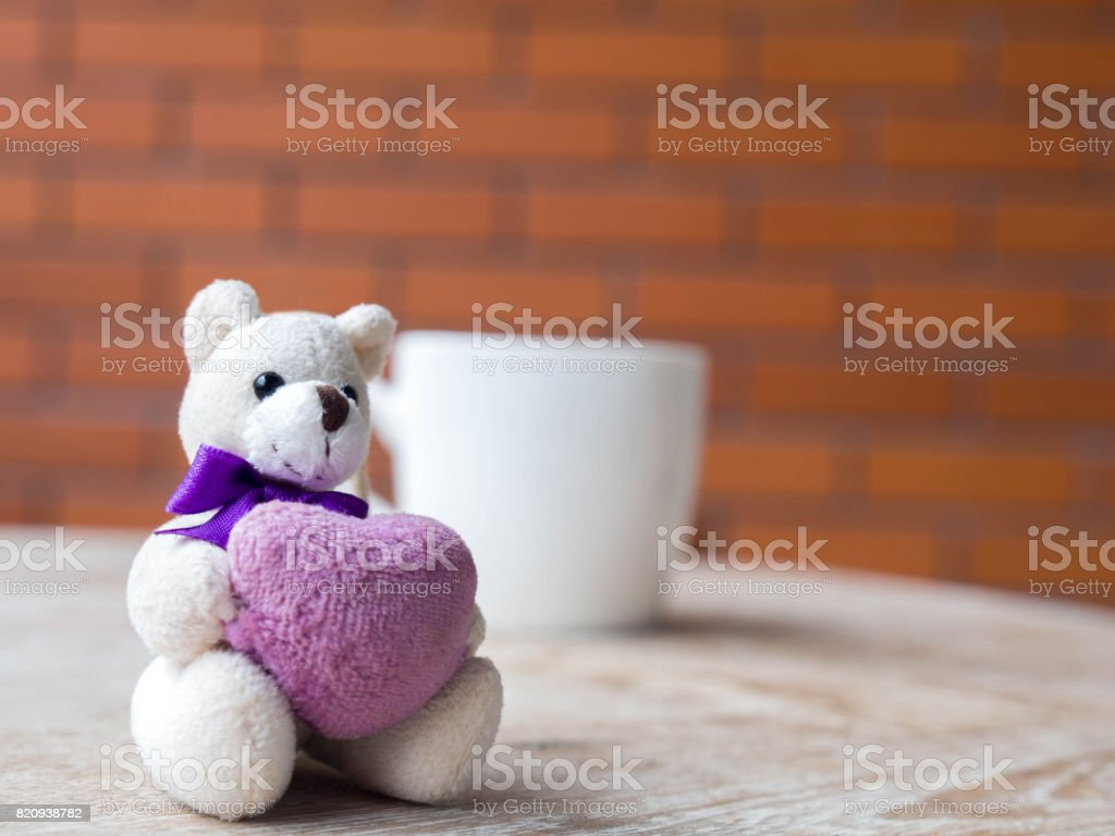 Teddy bear holding a purple heart. Live in a white cup of coffee. Placed on a wooden desk. The backdrop is a brick block of brown. stock photo