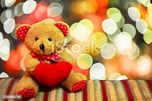 Teddy bear holding a red heart-shaped  pillow on Bokeh background, Valentine's day concept