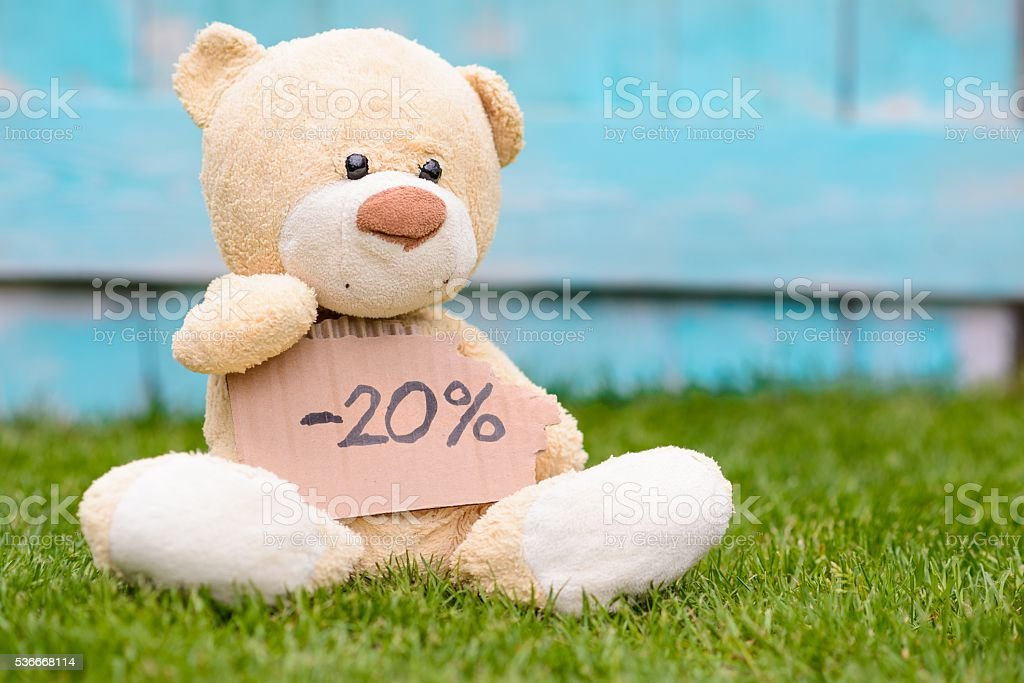 Teddy bear holding cardboard with information -20% stock photo