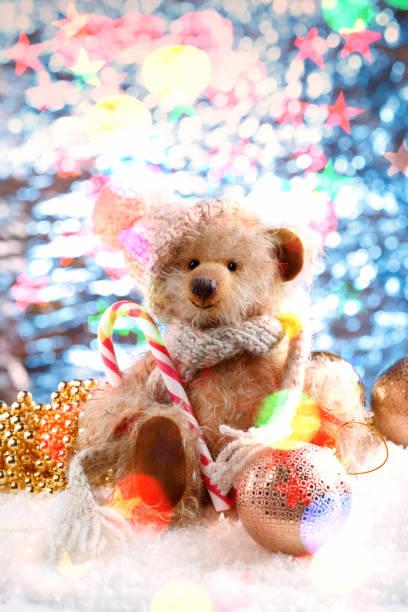 teddybär in eine wintermütze und weihnachtsdekorationen auf schnee - schal mit sternen stock-fotos und bilder