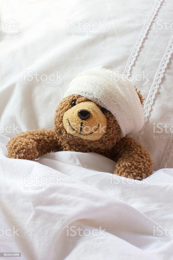 Teddy bear in bed with bandage on head - foto de stock