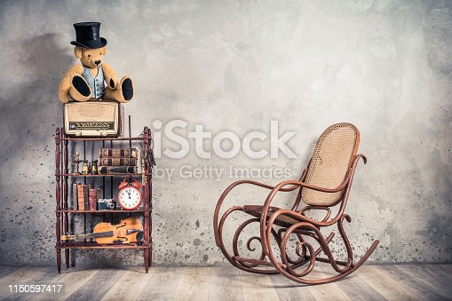 1065736660 istock photo Teddy Bear in cylinder hat on vintage radio, antique books, clock, camera, binoculars, fiddle, keys on shelf, aged rocking chair front concrete wall background. Retro old style filtered photo 1150597417