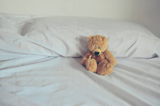 Teddy Bear in white bed stock photo