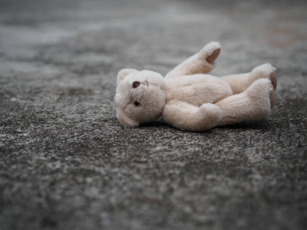 teddy bear is laying down on the floor. lonely concept. international missing children's day. - teddy bear stock photos and pictures