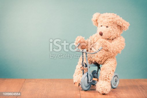 Teddy Bear is sitting on old retro toy bicycle in front mint green background. Vintage style filtered photo