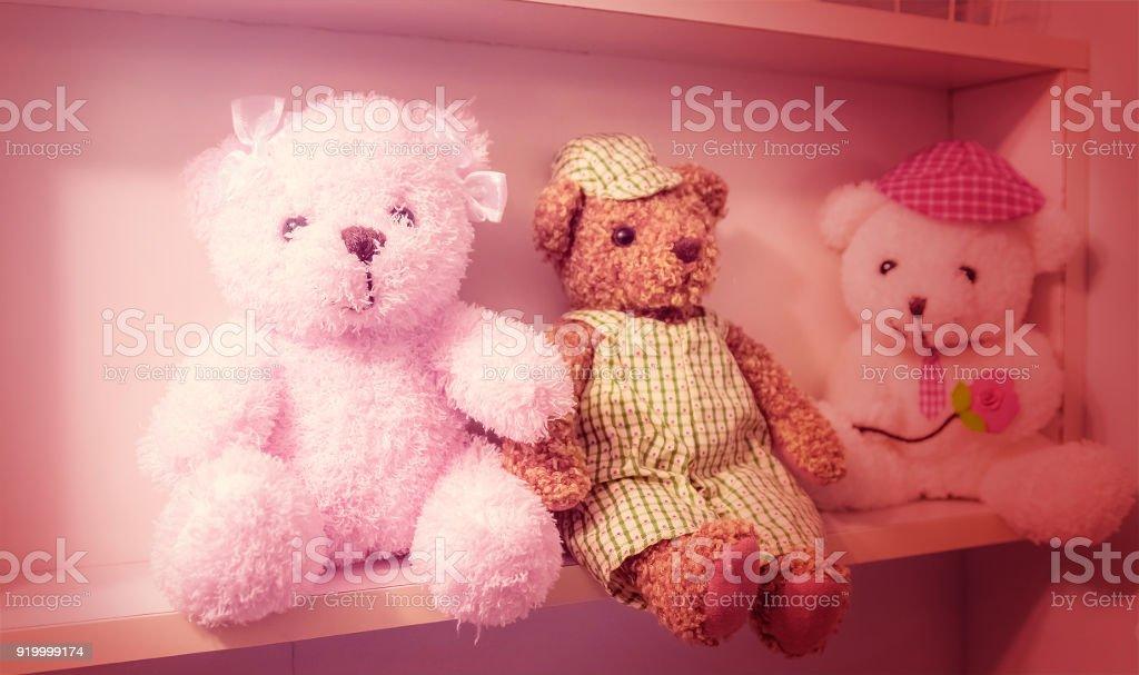 Teddy bear lay lined on a wall. stock photo