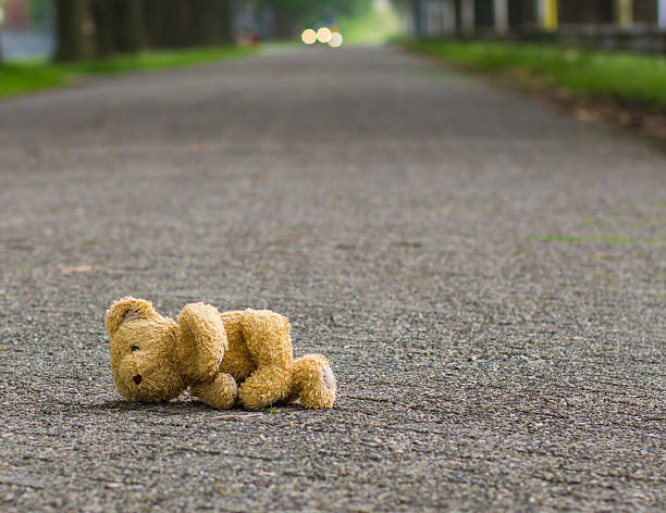 teddy bear lies on the road - abandoned stock photos and pictures