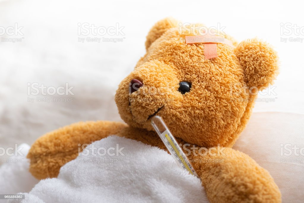 Teddy bear lying sick in hospital bed with with thermometer and plaster. Healthcare and medical concept. royalty-free stock photo