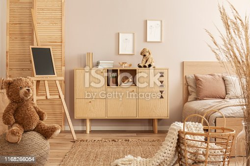 istock Teddy bear on pouf and small blackboard on easel in stylish kid's bedroom with wooden cabinet and beige bedding on bed 1168266054