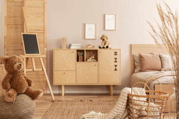 Teddy bear on pouf and small blackboard on easel in stylish kid's bedroom with wooden cabinet and beige bedding on bed Teddy bear on pouf and small blackboard on easel in stylish kid's bedroom with wooden cabinet and beige bedding on bed girl bedroom stock pictures, royalty-free photos & images
