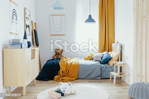 istock Teddy bear on single wooden bed in blue and orange bedroom interior 1156142610