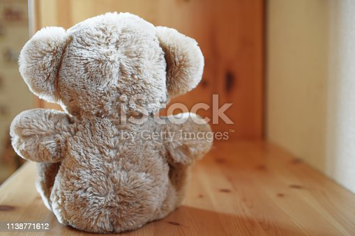 Teddy bear plush toy sitting on wooden table, close up back view with copy space for text.