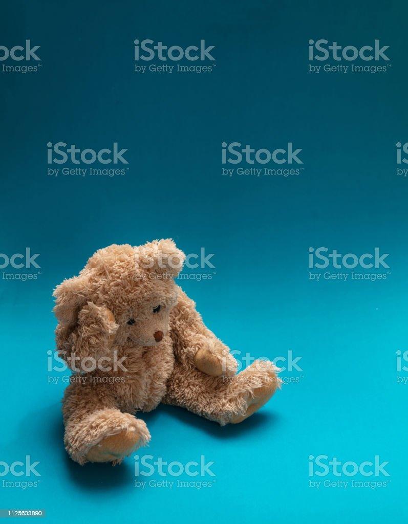 Blue Monday, depression concept. Teddy bear sad, holding his head,...