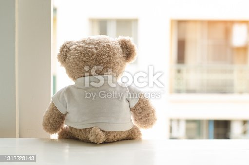 Lonely teddy bear in white t-shirt sitting by the window  with blurred background of apartment building, vintage tone.