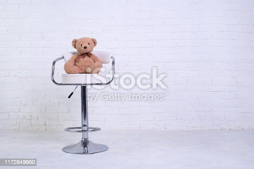 Teddy bear sitting on a chair against the background of a white brick wall, free space. Children's toy.