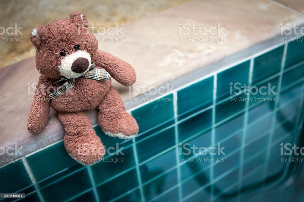 Teddy bear sitting on the pool edge stock photo