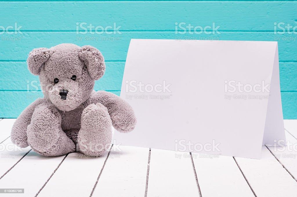 Urso de pelúcia sentado em branco piso de madeira em Azul-Verde - foto de acervo