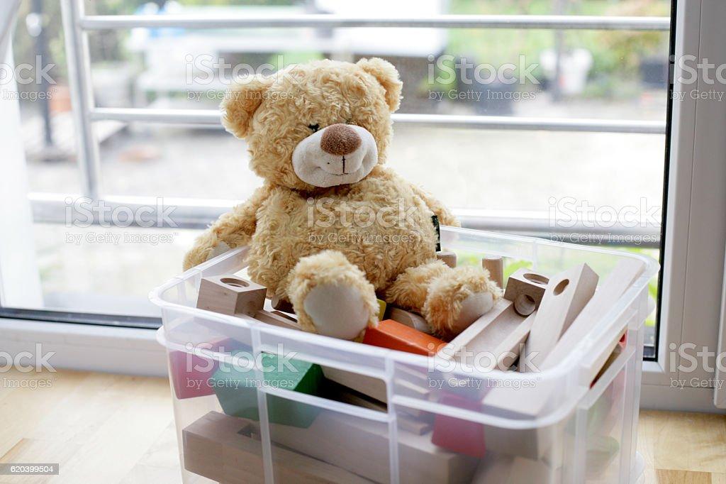 Teddy Bear sitting on wooden toys stock photo
