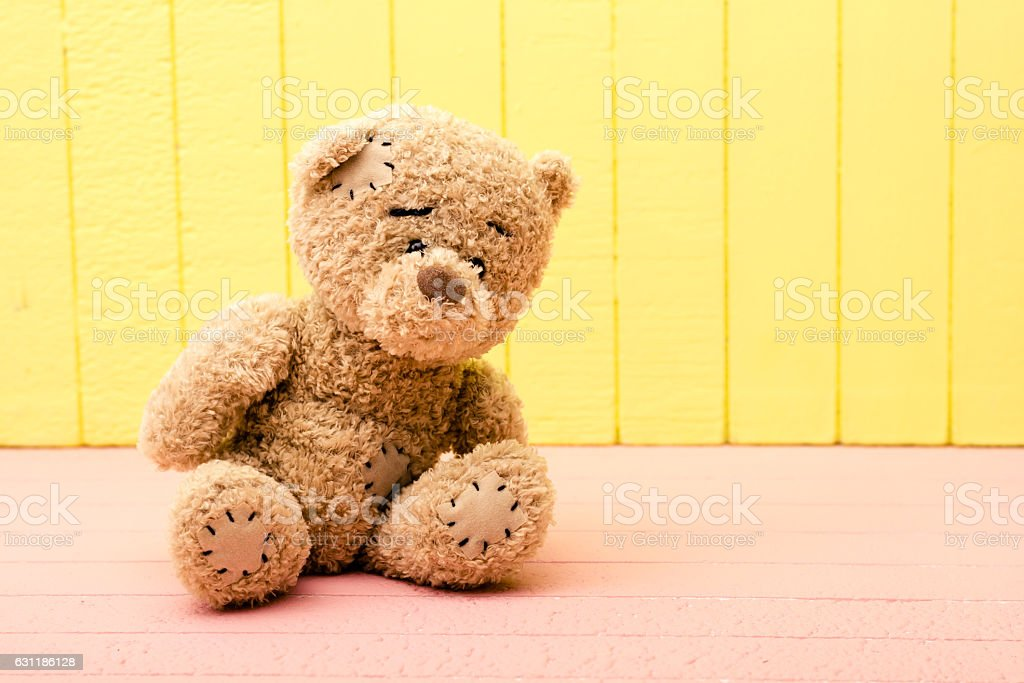 Teddy Bear toy alone on wood in front yellow rosy background