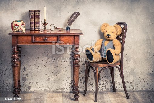 istock Teddy Bear toy on chair, quill ink pen with old inkwell, antique books, brass magnifying glass, candle in vintage candlestick, carnival mask on oak wooden table. Retro style filtered photography 1150815966