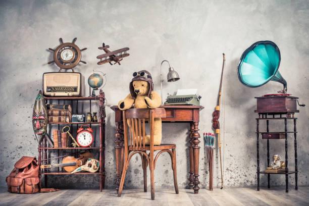Teddybären-Spielzeug auf Stuhl, Schreibmaschine, Vintage-Grammophon, alte Bücher, Radio, Globus, Fernglas, Karnevalsmaske, Kamera, Geige auf Regal, Lenkrad, Flugzeug, Reiselack, Bogen. Retro-Stil Foto – Foto