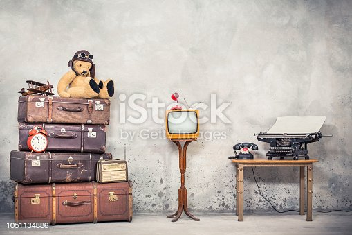 istock Teddy Bear toy with leather aviator's hat and goggles sitting on retro old travel suitcases, wooden plane, alarm clock, TV, mic, telephone and typewriter. Loft storage. Vintage style filtered photo 1051134886