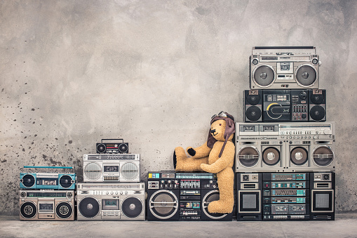 istock Teddy Bear toy with leather aviator's hat and goggles sitting on retro old school design ghetto blaster boombox stereo radio cassette tape recorders tower from circa 80s. Vintage style filtered photo 1074826034