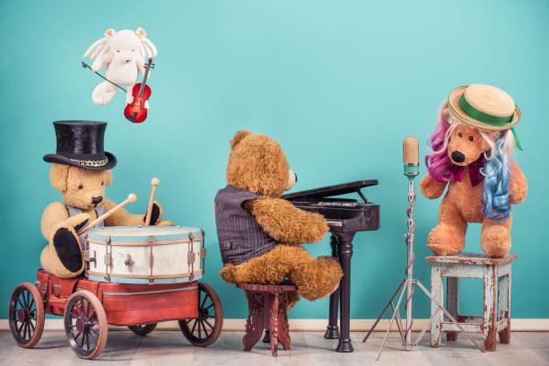 Teddybär Spielzeug Musikband: Sänger mit farbigen Haaren, Retro alte Mikrofon, Bär in Zylinder Hut spielen Trommel, fliegenden Engel mit Geige, Flügelspieler. Vintage Nostalgie Stil gefiltert Foto – Foto