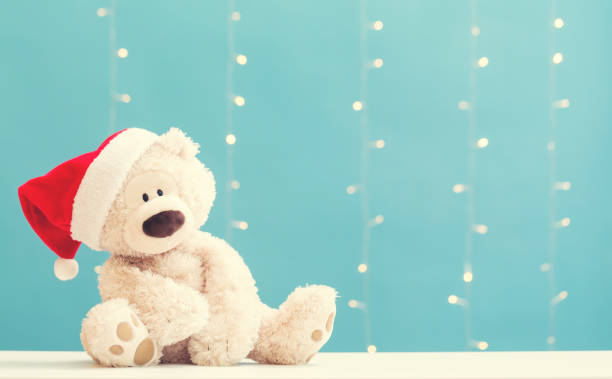 Teddy bear wearing a Santa hat Teddy bear wearing a Santa hat on a shiny light blue background christmas teddy bear stock pictures, royalty-free photos & images