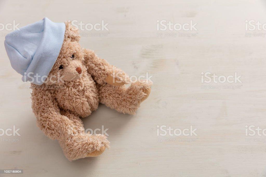 Ours en peluche vêtu pastel bleu cap sur fond en bois, espace copie - Photo