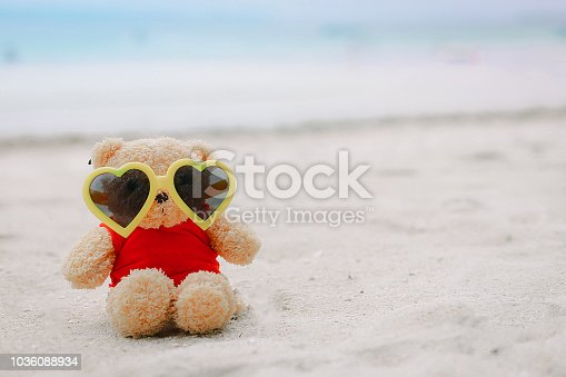 Teddy Bear wearing yellow heart-shaped glasses sitting on the sand with sky and blue sea as the background, Summer on the beach.