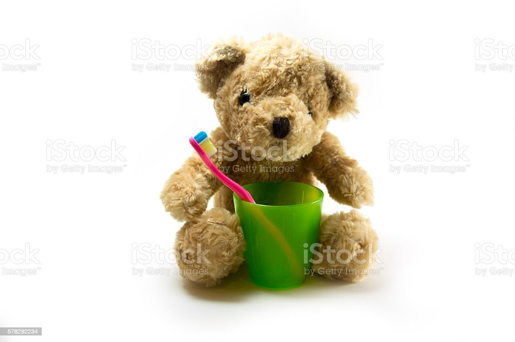 Teddy bear with a kid toothbrush and plastic glass stock photo