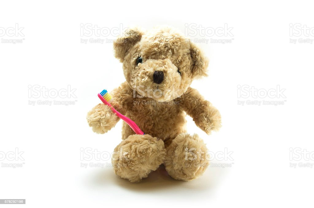 Teddy bear with a kid toothbrush stock photo