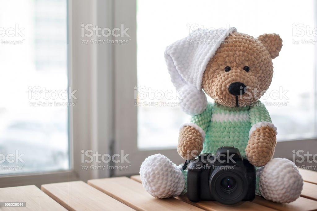 Oso de peluche con cámara en la mesa de madera. Copia espacio. Enfoque selectivo - foto de stock