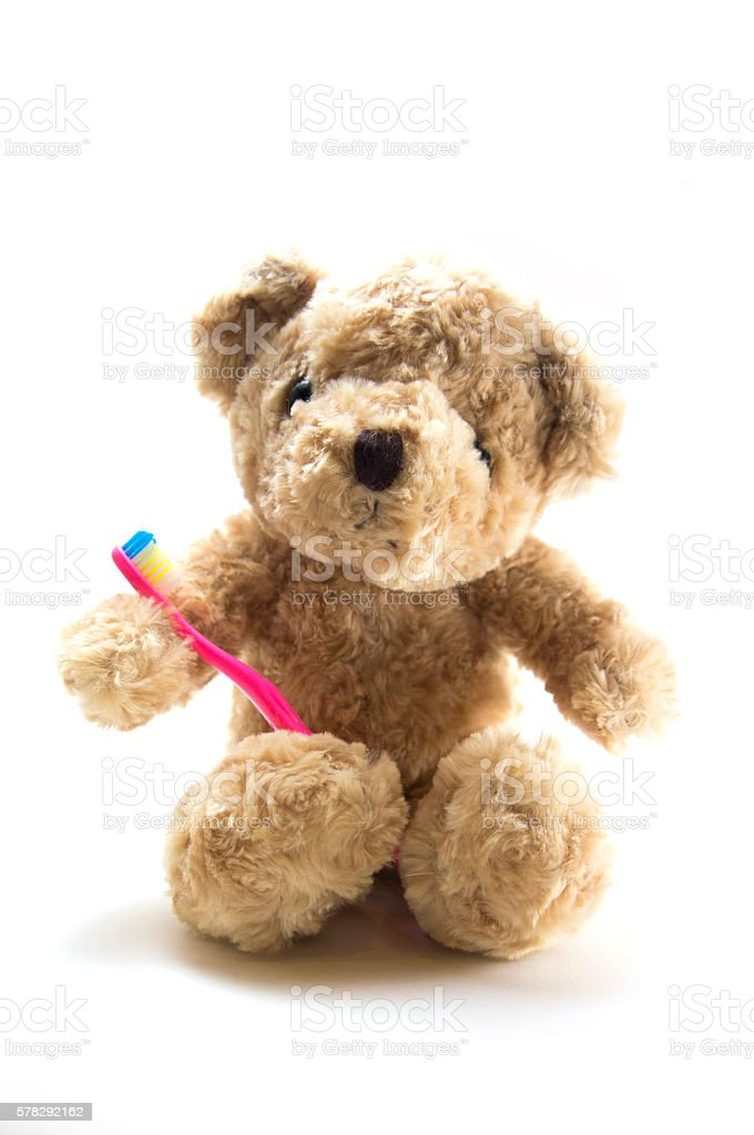 Teddy bear with kid toothbrush stock photo