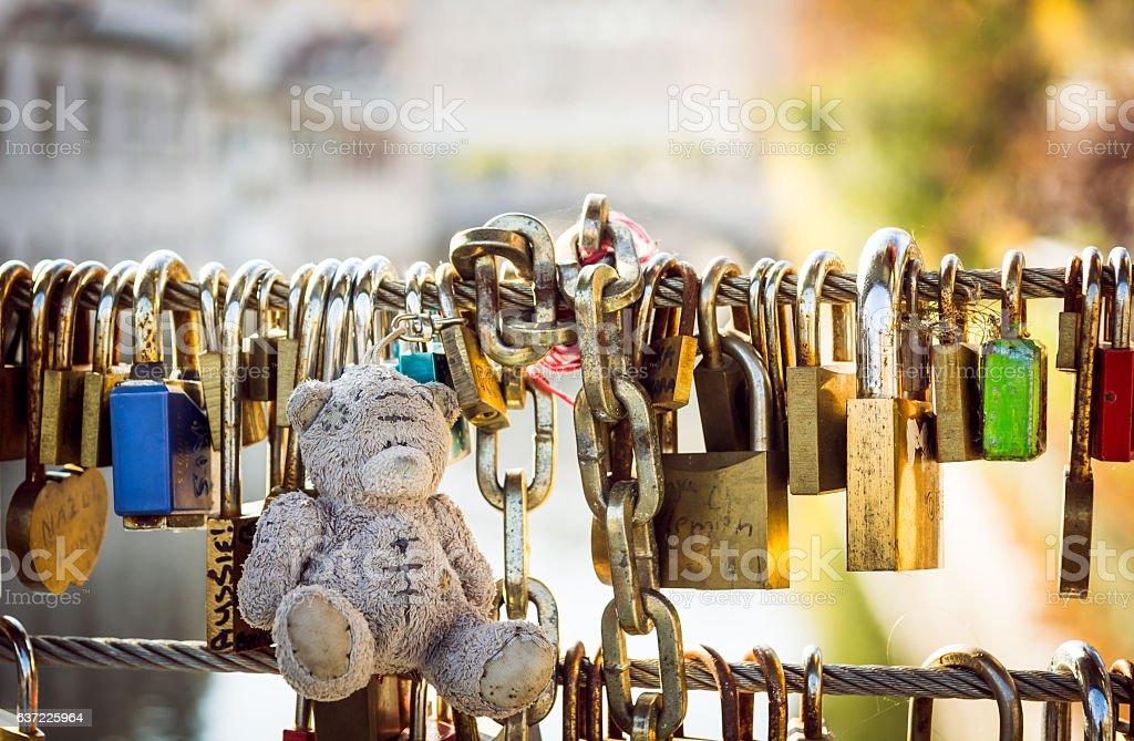 Teddy bear with love locks on a metal bridge. - Photo