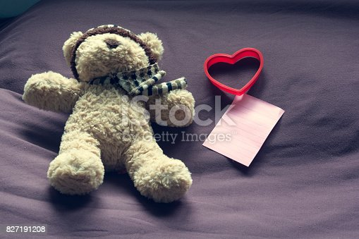 1061427386 istock photo Teddy bear with red heart shape and empty note paper on bed. Valentine concept. 827191208